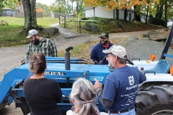 A small group stands around a blue, Ford tractor.