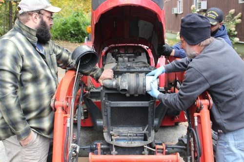 Two men on either side of a tractor with its hood open remove the air filter.