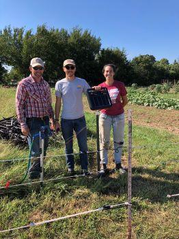 Kenny Simon, Luke Freeman, and Jenni Vaughan set up an electric deer fence.